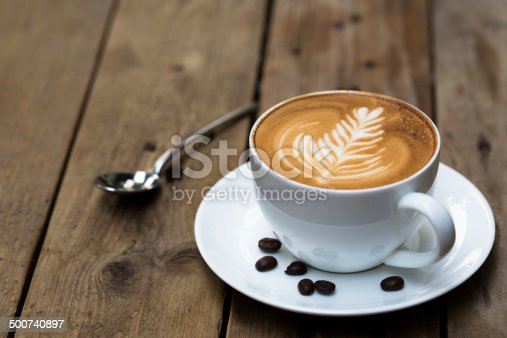istock Cup of hot latte art coffee on wooden table 500740897