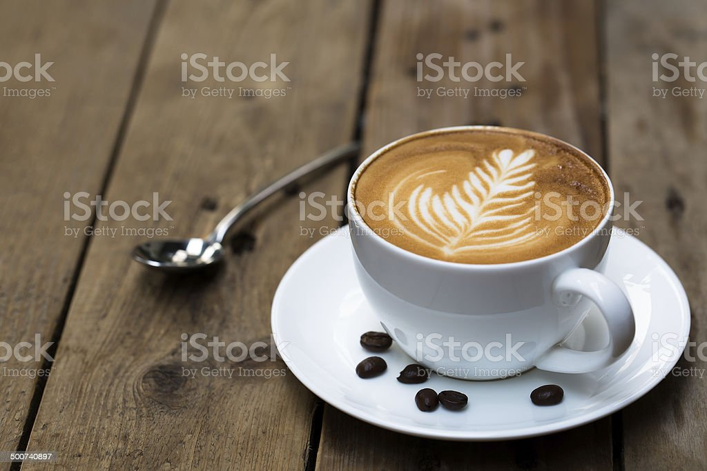 Cup of hot latte art coffee on wooden table stock photo