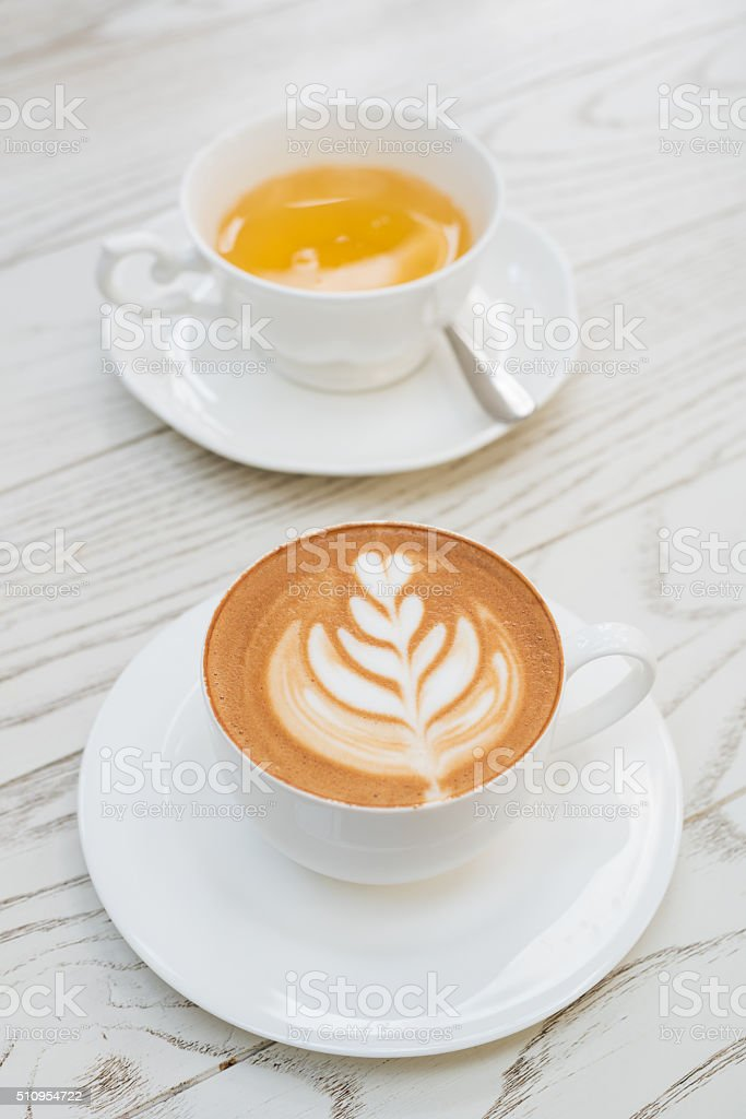 cup of hot latte art coffee with tea stock photo