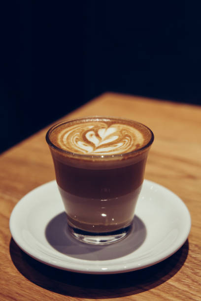 A cup of hot latte art on wooden table stock photo