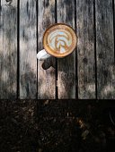 Image of hot latte coffee with latte art on vintage grunge wood textured background.