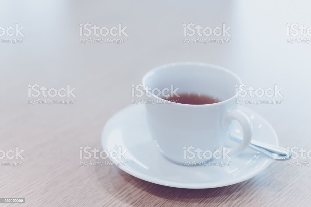 cup of hot tea and spoon on wooden table in meeting room - filter retro color tone zbiór zdjęć royalty-free