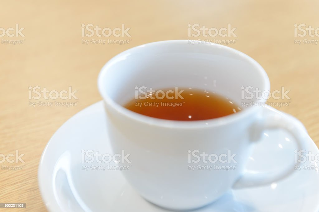 cup of hot tea and spoon on wooden table in meeting room royalty-free stock photo