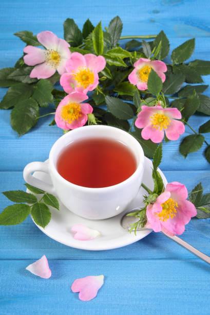 Tasse heißen Tee und wilde Rosenblume auf blauen Brettern – Foto