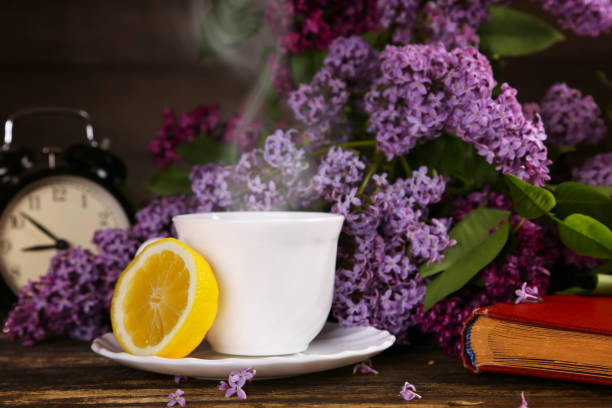 A cup of hot tea with a lemon and over a lilac flowers backdrop stock photo