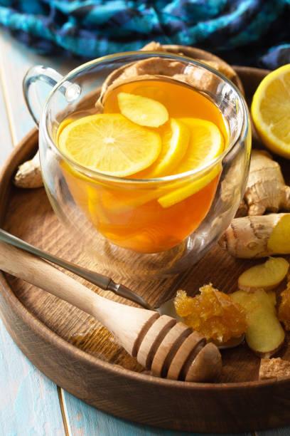 레몬, 생강, 벌집, 꿀을 나무 테이블에 가까이 올려 뜨거운 차 한 잔. 스톡 사진