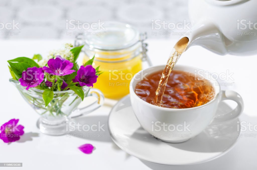 Cup of hot tea with mint and honey on white background. The process of pouring tea. Selective focus. Cup of hot tea with mint and honey on white background. The process of pouring tea. bouquet of flowers and mint leaves.Selective focus. Black Tea Stock Photo