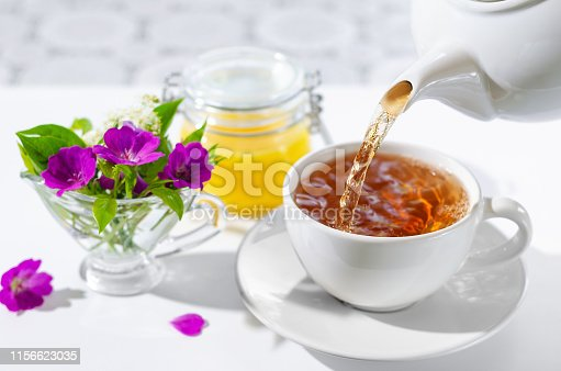 Cup of hot tea with mint and honey on white background. The process of pouring tea. bouquet of flowers and mint leaves.Selective focus.