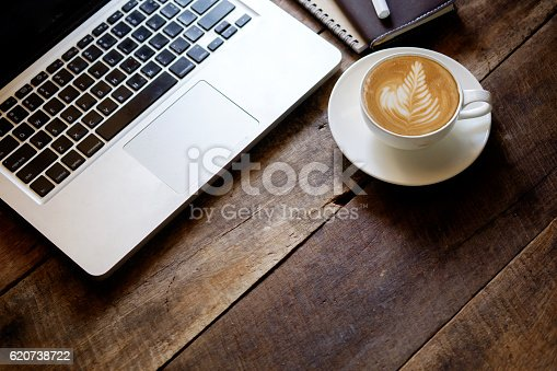 istock cup of latte art coffee and Laptop on wood table. 620738722