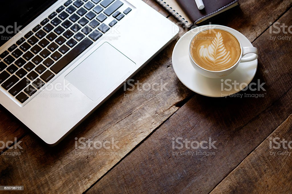 cup of latte art coffee and Laptop on wood table. stock photo