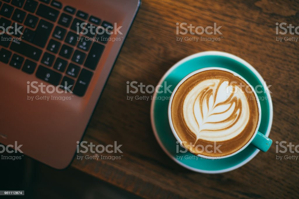 Cup of latte art coffee and Laptop on wood table stock photo