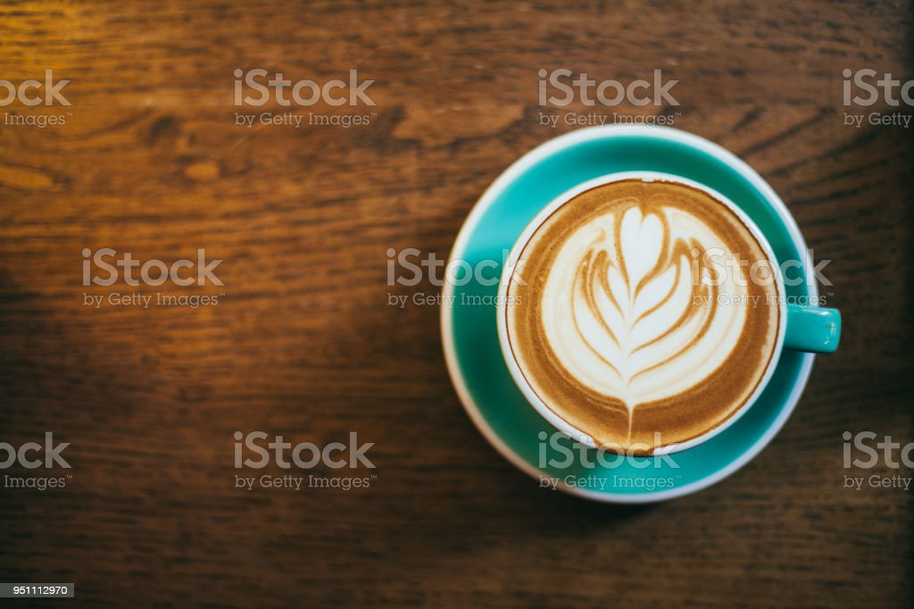 Cup of latte art coffee on wood table stock photo