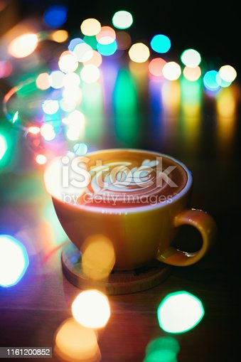A cup of latte on wooden table with decoration lights