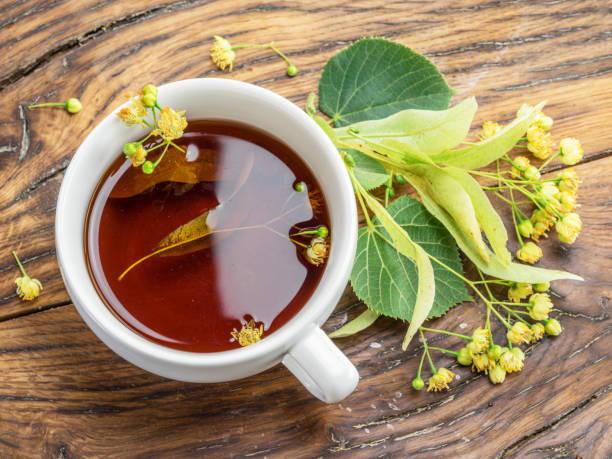 Cup of linden tea and lime flowers on the wooden table. Top view. stock photo
