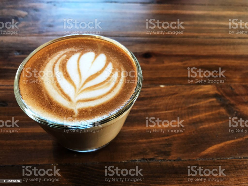 Cup of love , heart latte art coffee in Glass on the vintage wooden...