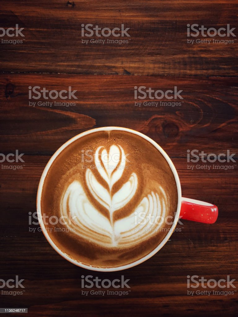 Cup of love , heart latte art coffee in white cup on the vintage...