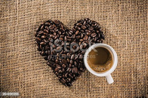 Cup of Macchiato coffee with roasted raw coffee beans making a heart shape on jute background