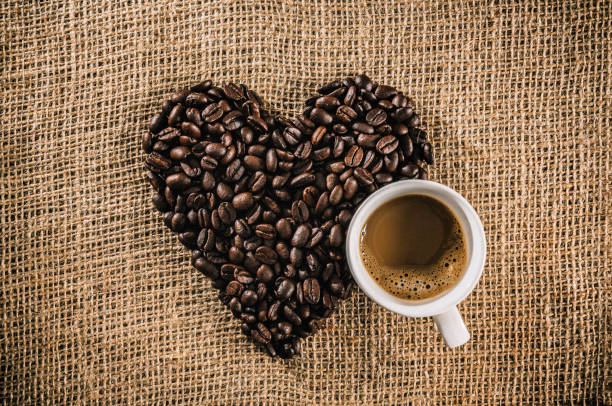 Cup of Macchiato coffee with roasted raw coffee beans making a heart shape on jute background stock photo