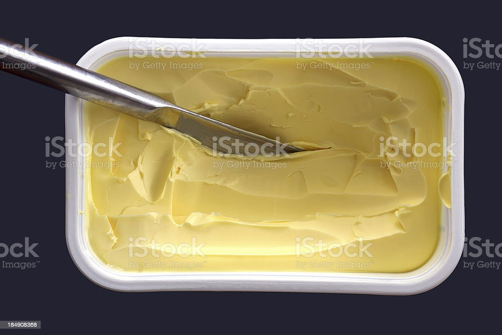 Cup of margerine with knife in it, isolated top view royalty-free stock photo