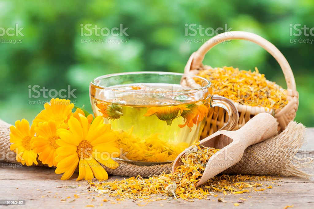 Cup of  marigold tea and calendula flowers. stock photo