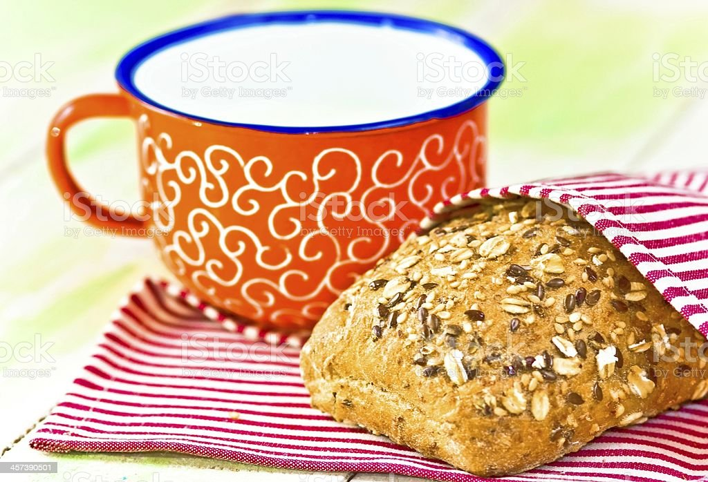 Cup of milk and bread on napkin royalty-free stock photo
