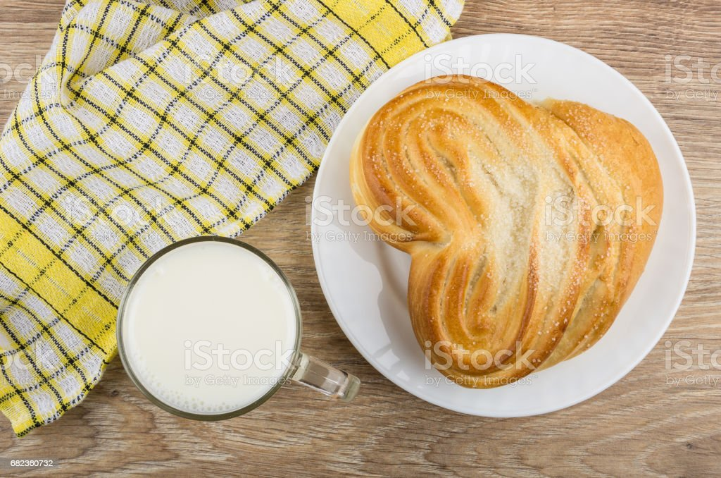 Cup of milk, checkered napkin and bun with sugar royalty free stockfoto