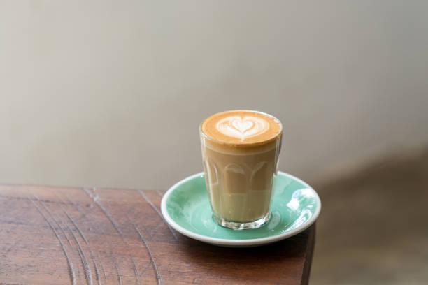 einen cup piccolo-latte kaffee mit latte art und grün untertasse. - kleiner couchtisch stock-fotos und bilder
