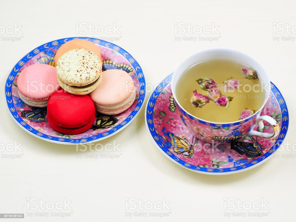 Cup of rose bud tea served with French macarons stock photo