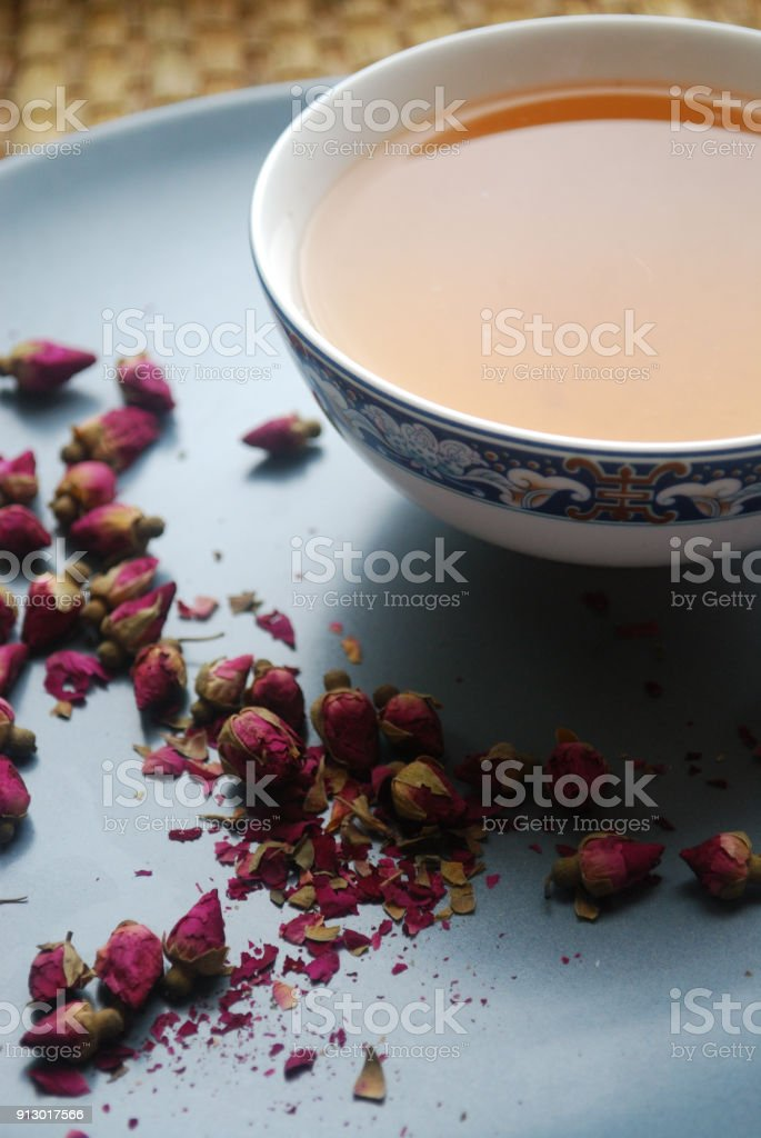 Cup of rose tea with rosebuds on the plate. stock photo