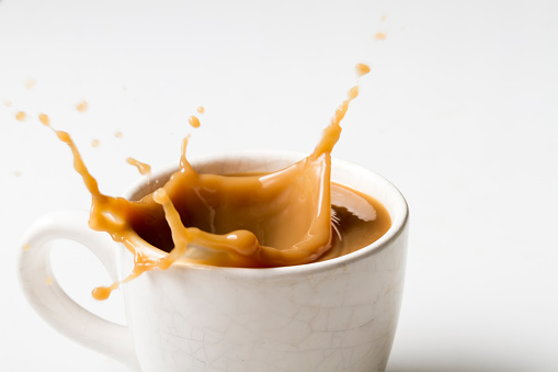 Cup of splashing coffee on white background