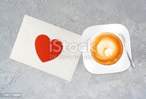 A cup of tasty cappucino and valentine letter with heart. Top view. Romantic meeting concept. Stone texture table background.