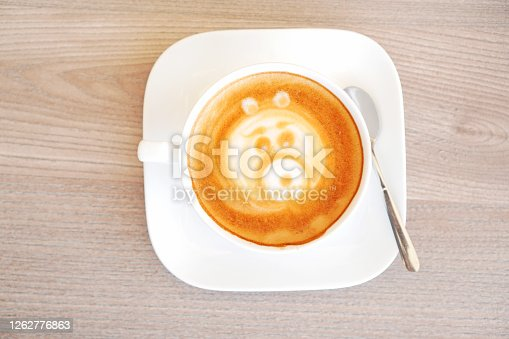 A cup of tasty cappucino. Top view. Wood texture table background.