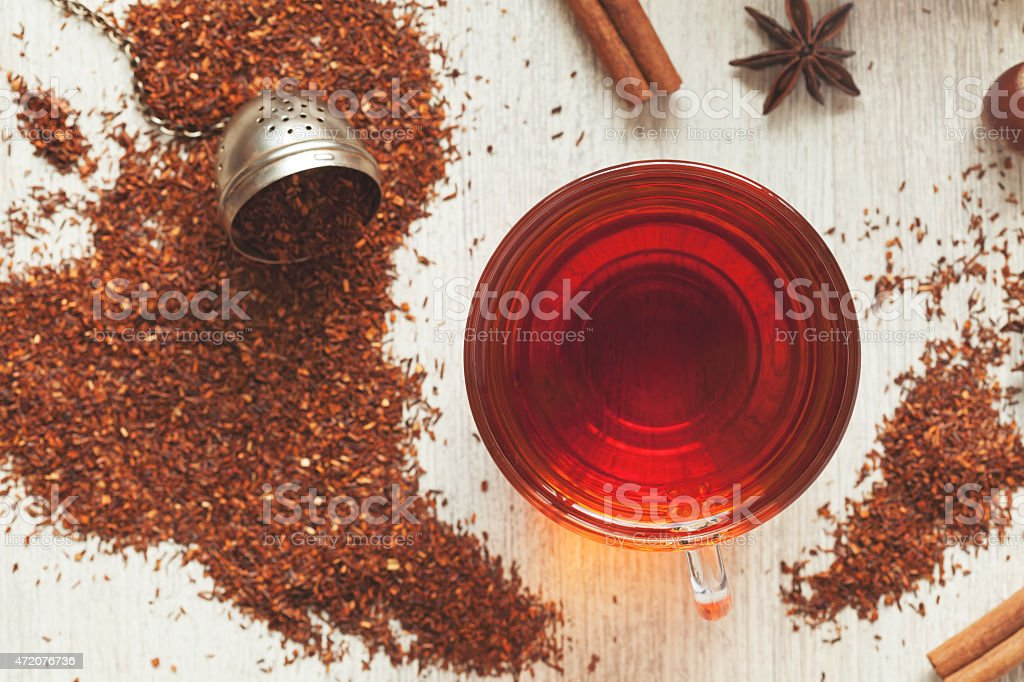 Cup of tasty organic herbal rooibos red tea with spices stock photo