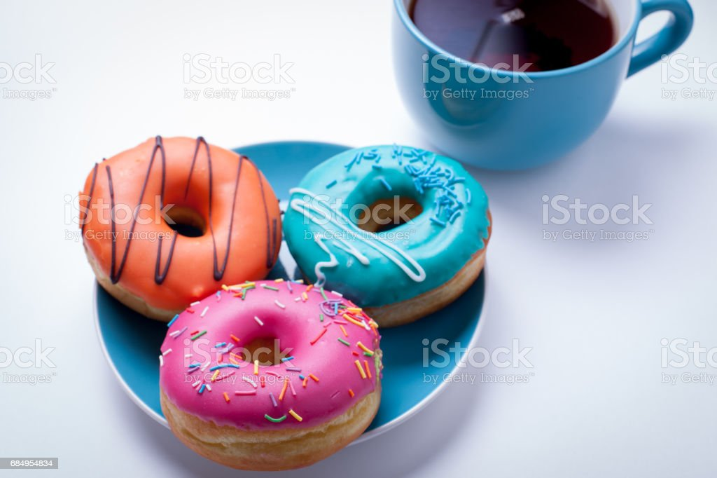 A cup of tea and a plate with donuts in a glaze on an white background Lizenzfreies stock-foto