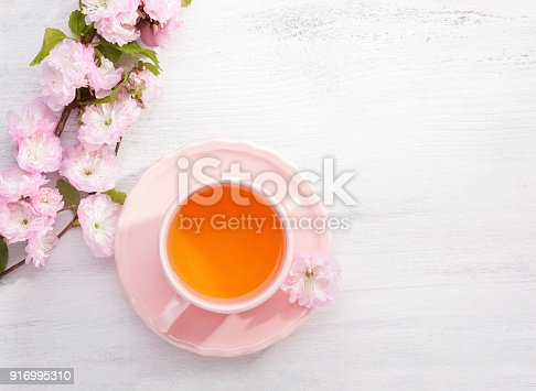 Cup of tea and  blossoming Almond (Prunus triloba) branch  on rustic table.