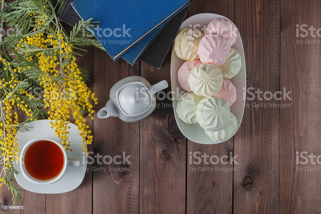 Cup of tea and books on wooden table stock photo