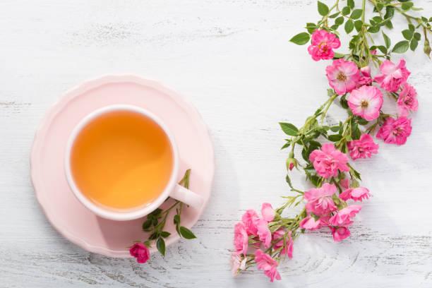 tasse tee und zweig der rosen auf rustikalen tisch. - rosen tee stock-fotos und bilder