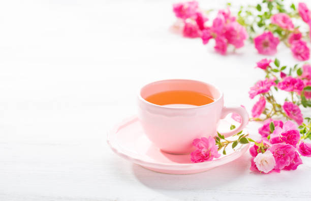 Cup of tea and branch of small pink  roses on  white rustic table. stock photo