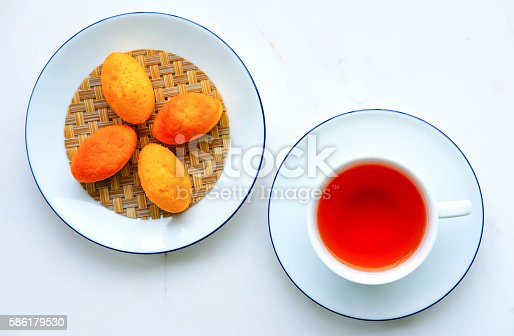 cup of tea and Madeleine on white marble desk