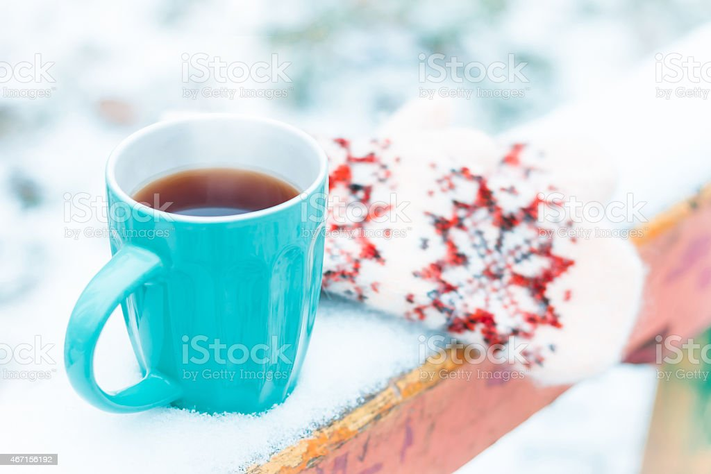 cup of tea and mittens on wooden bench stock photo