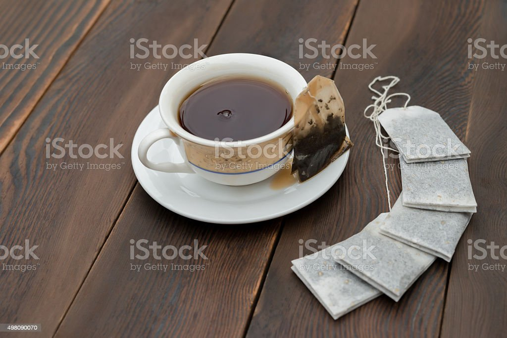 cup of tea and new teabags on a wooden background stock photo
