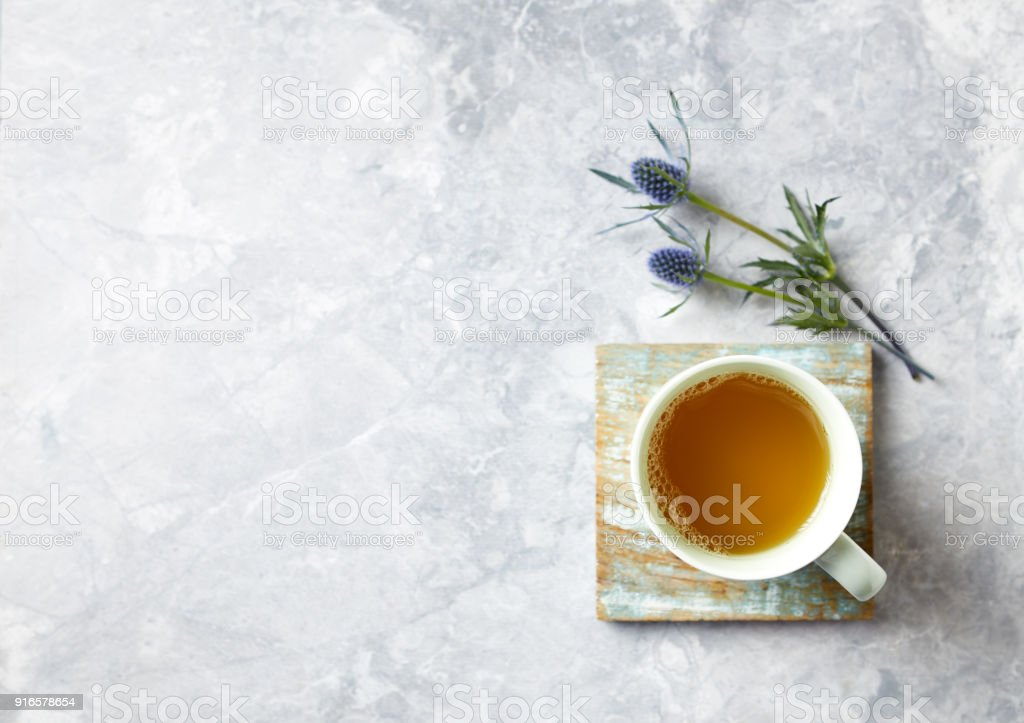 Cup of Tea and Sea Holly Flowers on gray stone background stock photo