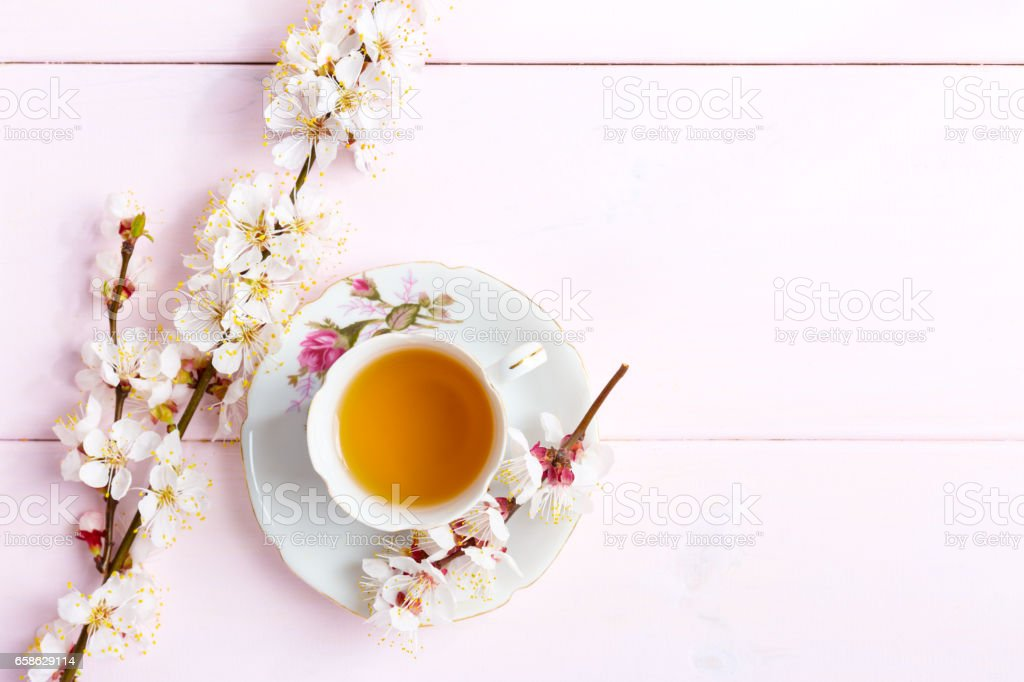 Cup of  tea and spring  flowers  on  light pink wooden table. stock photo
