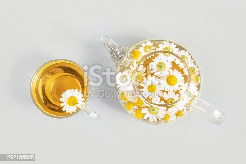 Cup of tea and transparent teapot with camomile flowers on yellow background. Chamomile Tea Benefits Your Health concept. Top view. Trendy colors 2021.
