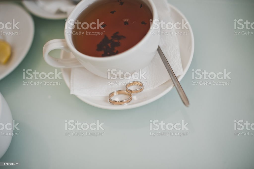Cup of tea and wedding rings 6803. photo libre de droits