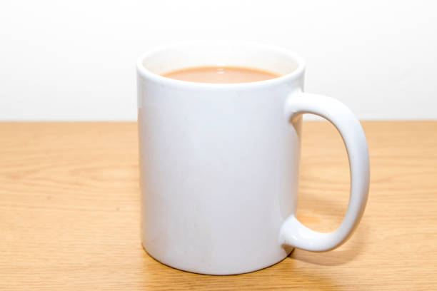 Cup of tea in a white mug with milk stock photo