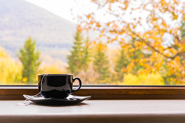 cup of tea in front of window with autumn view. - mountain home interieur stock-fotos und bilder