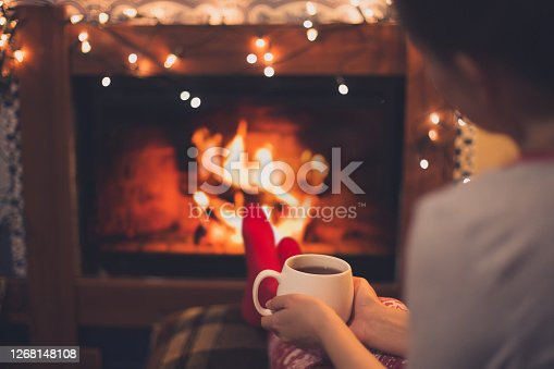 istock Cup of tea in woman's hands sitting near fireplace 1268148108