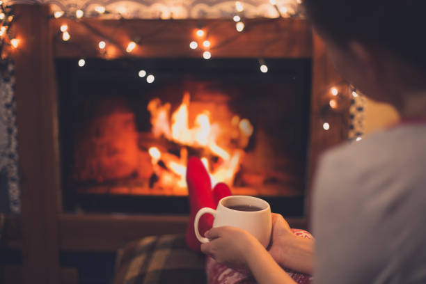 cup of tea in woman's hands sitting near fireplace - hygge imagens e fotografias de stock