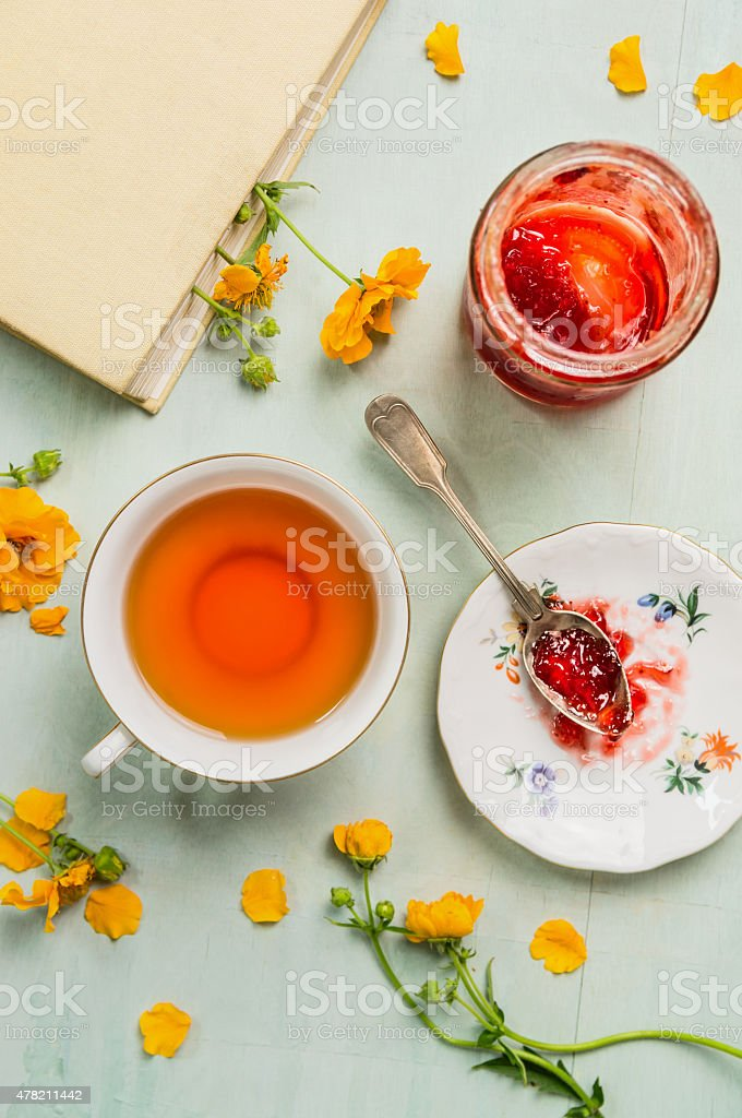 Cup of tea, jar with jam, book and yellow flowers stock photo